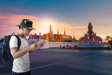 Asian man tourist is looking to the map, while traveling in Bangkok with most famous landmark is Wat Phra Kaeo at background.
