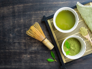 Green matcha tea in a bowl and bamboo whiskon on wood table,top view