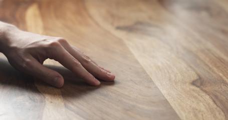 closeup of man hand checking hard wood surface