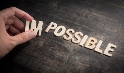 hand taking of the wooden letters in from the word impossible so it says possible.