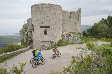 Mountain bikers riding cycle on pathway by ancient fort