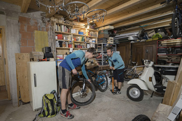 Men inflating bicycle at garage