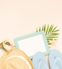 Empty frame and summer holidays items on creme background. Straw hat, blue flip flops and wood bracelet. Selective focus. Place for text. Flat lay, top view.