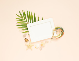 Empty frame and summer holidays items on creme background. Seashells and starfish. Selective focus. Place for text. Flat lay, top view.