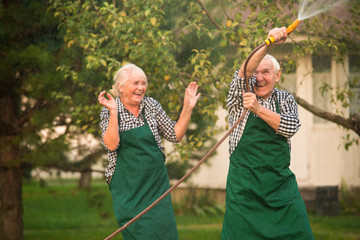 Cheerful people outdoors. Couple with garden hose.