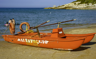 Lifeboat on the beach. The sea is calm and the bathers are at sea