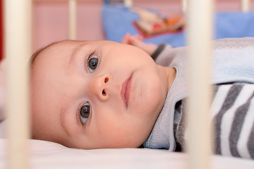 Baby boy lying on back in a white crib