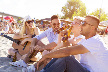 Group of friends playing guitar on the beach and having fun together