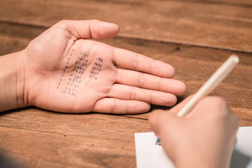 People cheating on test by writing answer on hand