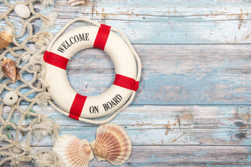 Nautica background with safety buoy with the text welcome on board seashells and fishing net on a blue scaffolding wooden background