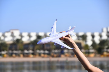 White airplane model transport in female hand