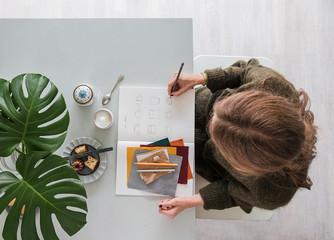Frau zeichnet Mode in ihrem Atelier