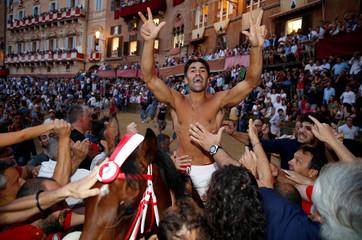 "Jockey Jonatan Bartoletti of the ""Giraffe"" ( Giraffe) parish celebrates after winning the Palio horse race in Siena"