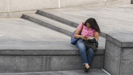 Lady using mobile phone sitting on a parapet near Tower Bridge in London, UK