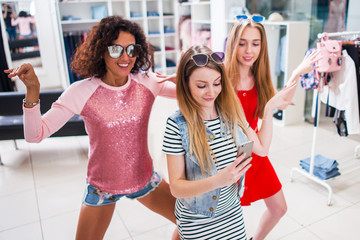 Smiling female friends having fun, making video or selfie while doing a funny dance in fashion showroom