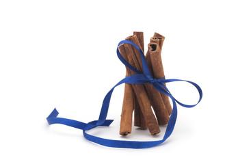 Cinnamon sticks with blue ribbon on white background