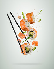 Flying sushi pieces with chopsticks, separated on soft background