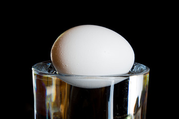 An egg floating in a glass of water.