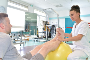 male patient during physical therapy praxis and female physiotherapist