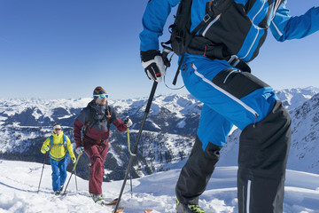 Skiers walking on snow mountain against sky