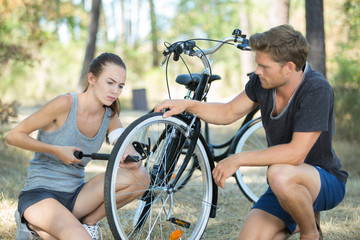 man and woman pumping up her bike