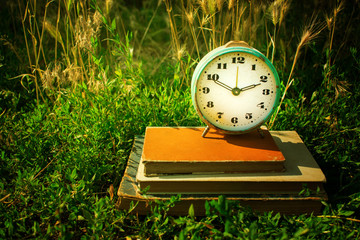 Vintage alarm clock on a stack of old books against a background of green grass