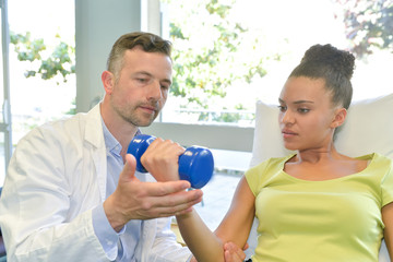 male physiotherapist exercising with patient holding dumbbell