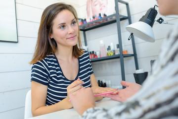 woman doing nail manicure