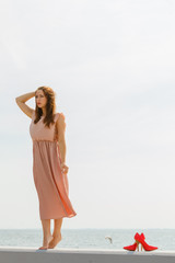 Woman wearing long light pink dress on jetty