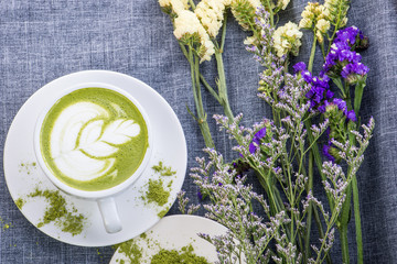 reen tea / Matcha latte in a cup with matcha powder on the wooden table