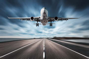Poster Avion à Moteur Airplane and road with motion blur effect. Landscape with white passenger airplane is flying in the cloudy sky over the asphalt road. Blurred. Passenger airplane is landing. Commercial plane. Aircraft