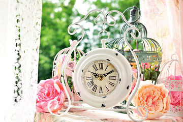 vintage style white clock and bird cages with flowers