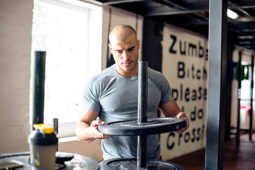 Man is preparing weights for exercise