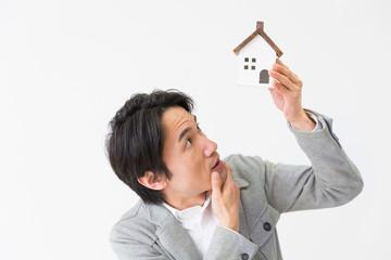 家のミニチュアを持つミドル男性 考える
