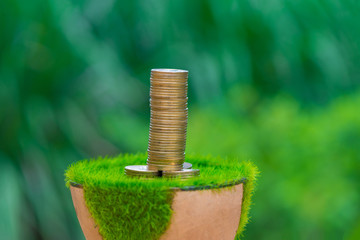 Stack of gold coin on artificial grass in pot, with green nature background.