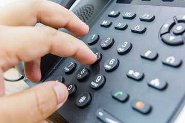 Closeup of male hand holding telephone receiver while dialing a telephone number to make a call using a black landline phone. Conceptual of global communication, business support and customer care.