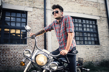 Handsome young man standing on vintage motorcycle