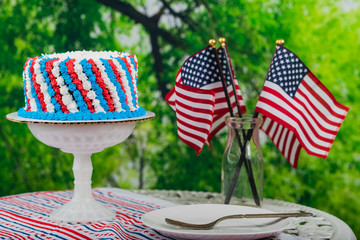 USA holiday with red white and blue cake, flags and decor and empty plate with fork.