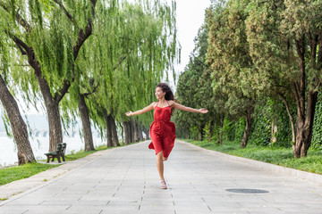 Wall Mural - Happy beautiful young woman dancing of freedom in summer park with trees in the background. Asian woman in red dress running of happiness.