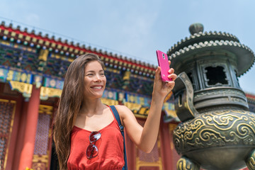 Girl taking phone selfie at china tourist attraction using smartphone at old temple bronze sculpture in Beijing, china. Asia tourism travel. People during vacation.
