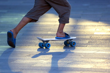 the legs of a teenager rolling on a skateboard.
