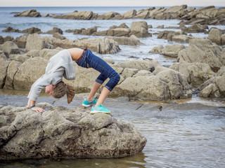 Girl in backflip position on rocks at beach