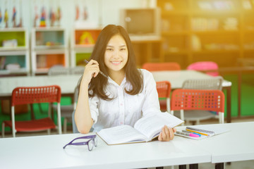 School education and literacy concept with Asian young girl student active learning reading book and smiling to camera while working in a high school library or classroom,vintage color