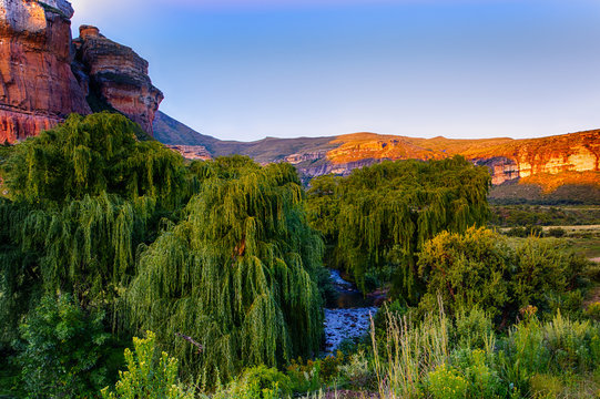 South Africa Drakensberge golden gate national park, scenic panoramic landscape with golden red rocks,mountains,trees, river  and a sunny blue sky