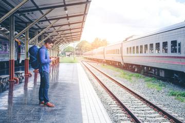 Traveler man  waits train on railway platform
