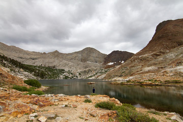 Man standing alone by lake and mountains