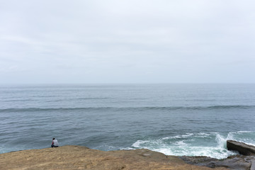 Man sitting alone on Sunset Cliffs in San Diego looking over ocean