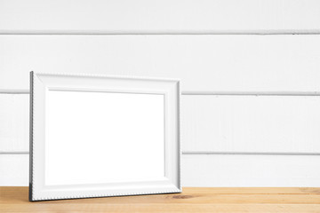 White picture frame put on wood table in white wood wall room.