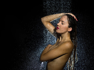 Attractive naked young woman taking a shower