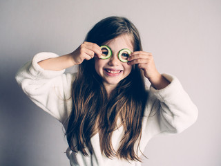 Little girl with cucumbers on her face, concept of beauty and health